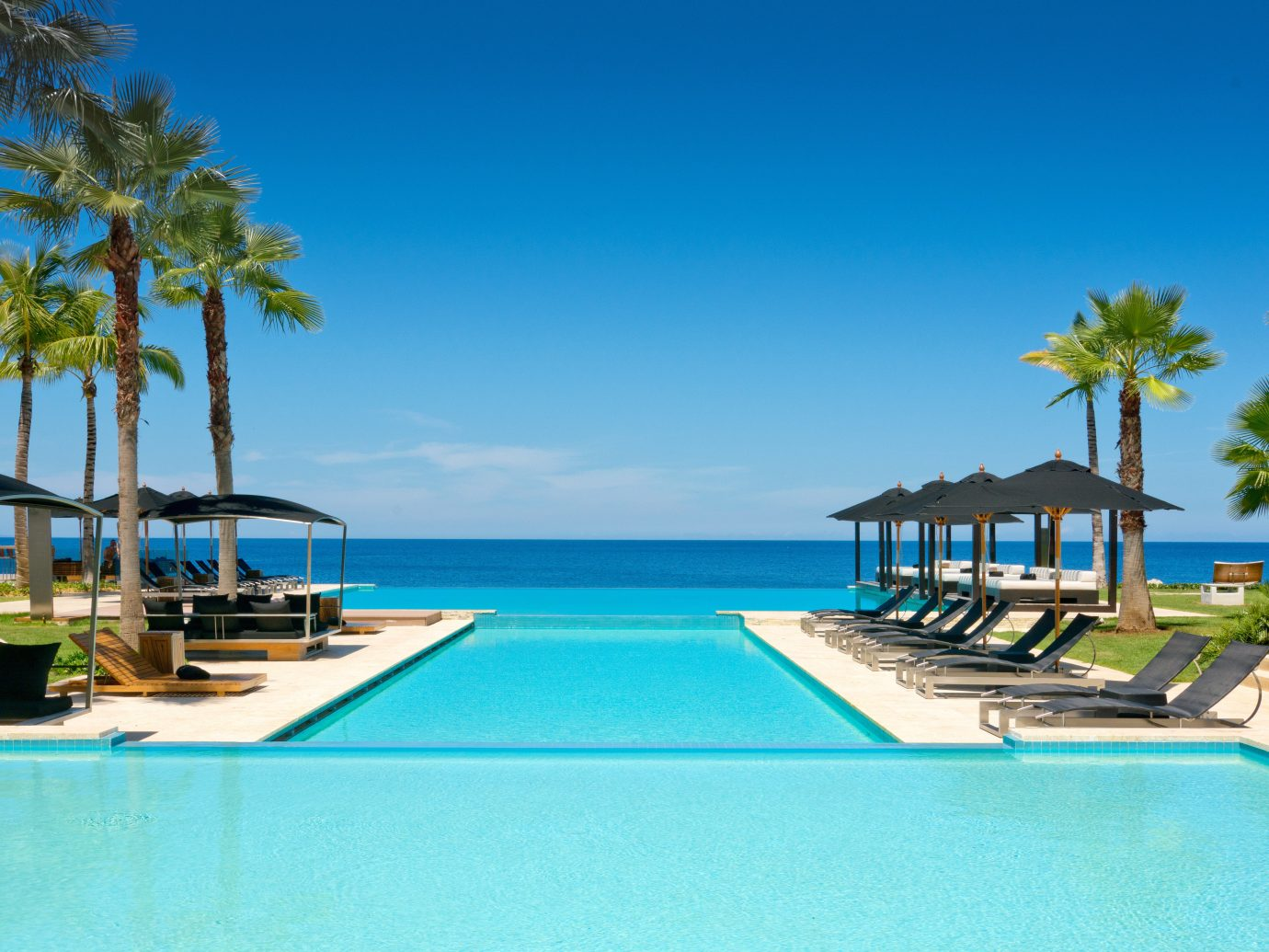 Beachfront Hotels Luxury Pool water sky outdoor Beach swimming swimming pool chair leisure blue property Resort vacation caribbean estate condominium resort town marina Sea bay Villa real estate Lagoon palm dock lined shore Island