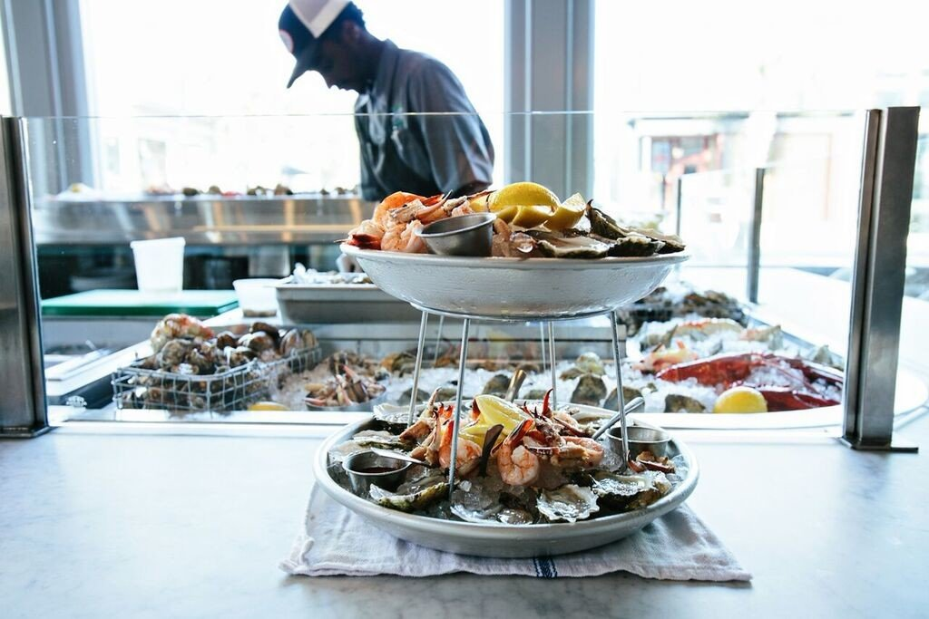 Eat food Food + Drink natural light oysters people Seafood table plate dish window meal cuisine barbecue grill buffet fish counter outdoor grill barbecue brunch sense restaurant meat cooking