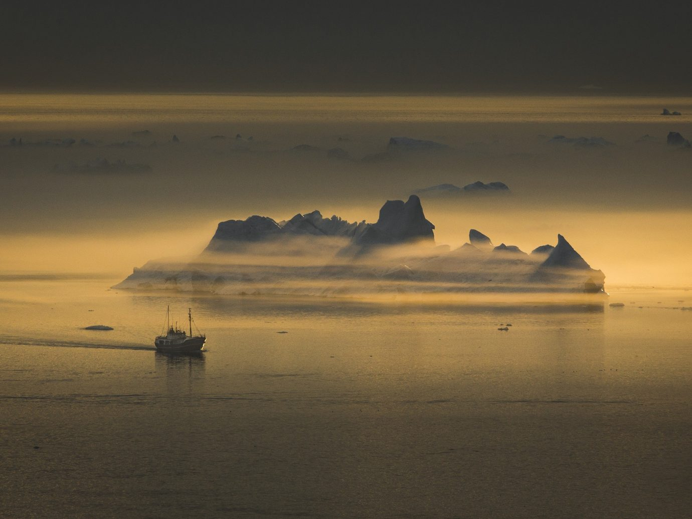A fishing vessel passes an iceberg near the Ilulissat ice fjord