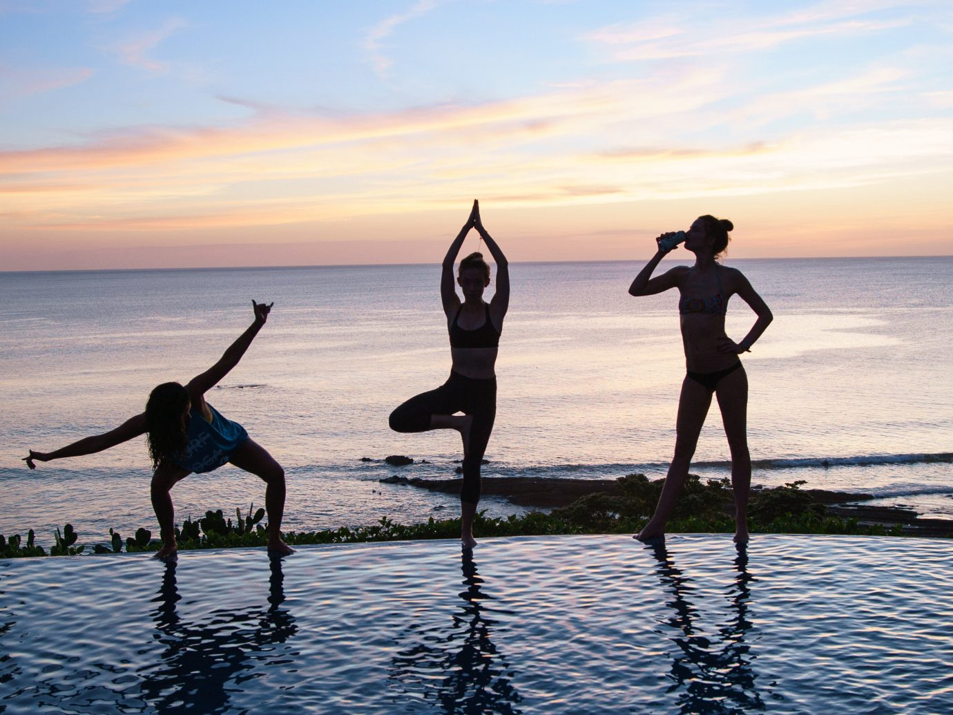 Health + Wellness Meditation Retreats Trip Ideas Yoga Retreats water sky outdoor Beach Sea Ocean physical fitness sports Sunset water sport silhouette surfing shore