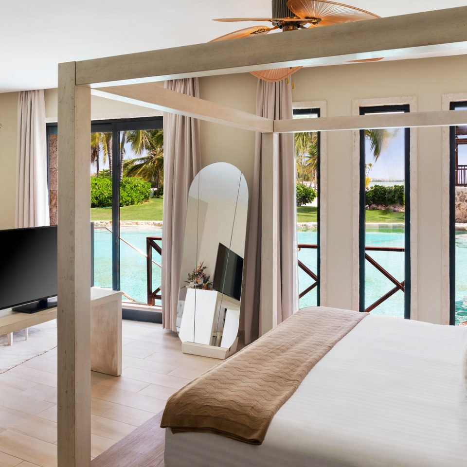 suite with bed and windows overlooking pool on first floor
