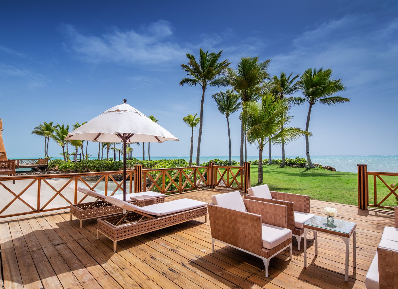 hard wood patio space with lounge chairs and regular seating chairs with cushions by the beach