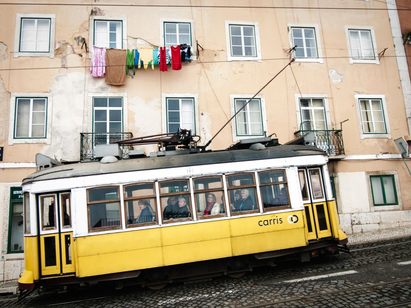 Trip Ideas building outdoor vehicle land vehicle tram transport yellow rolling stock public transport City metropolitan area cable car traveling past