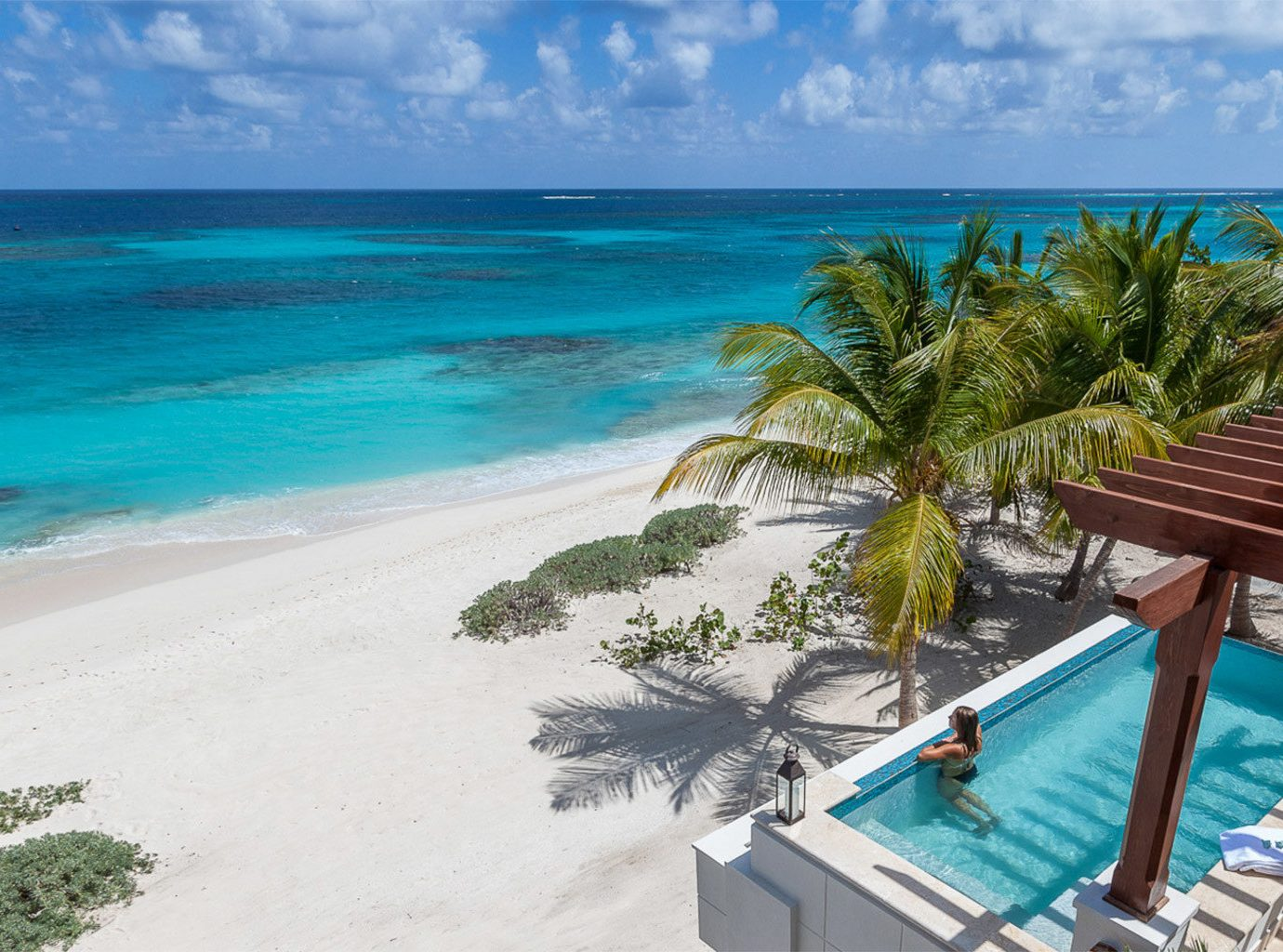 Hotels Trip Ideas water sky outdoor Beach Pool chair landform caribbean geographical feature Ocean vacation Sea body of water Nature shore Coast Resort bay tropics Lagoon cape Island lawn swimming pool swimming cay sandy palm empty reef overlooking Deck sunny day