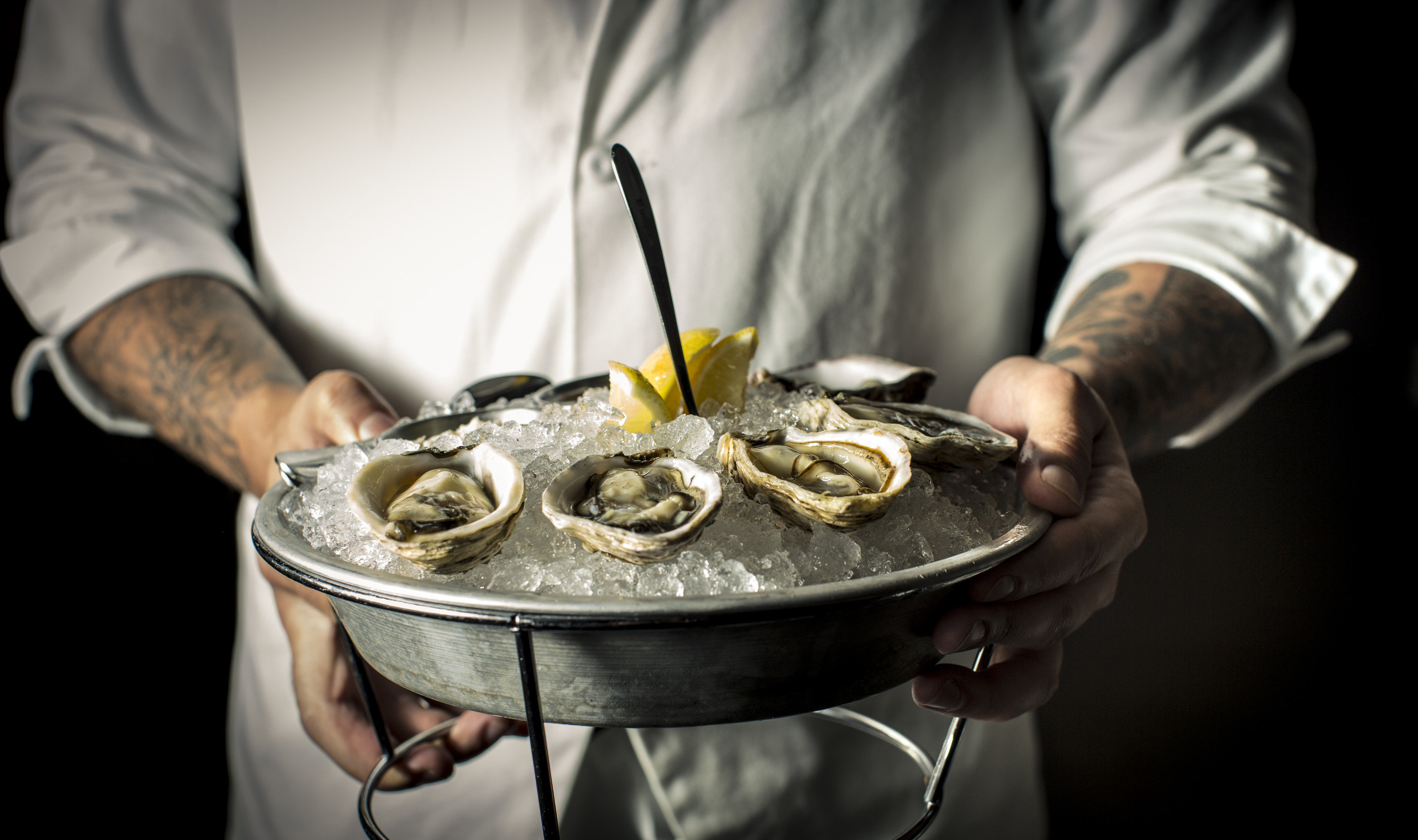 Food + Drink Travel Tips person oyster indoor food clams oysters mussels and scallops animal source foods Seafood mussel preparing pan cooking