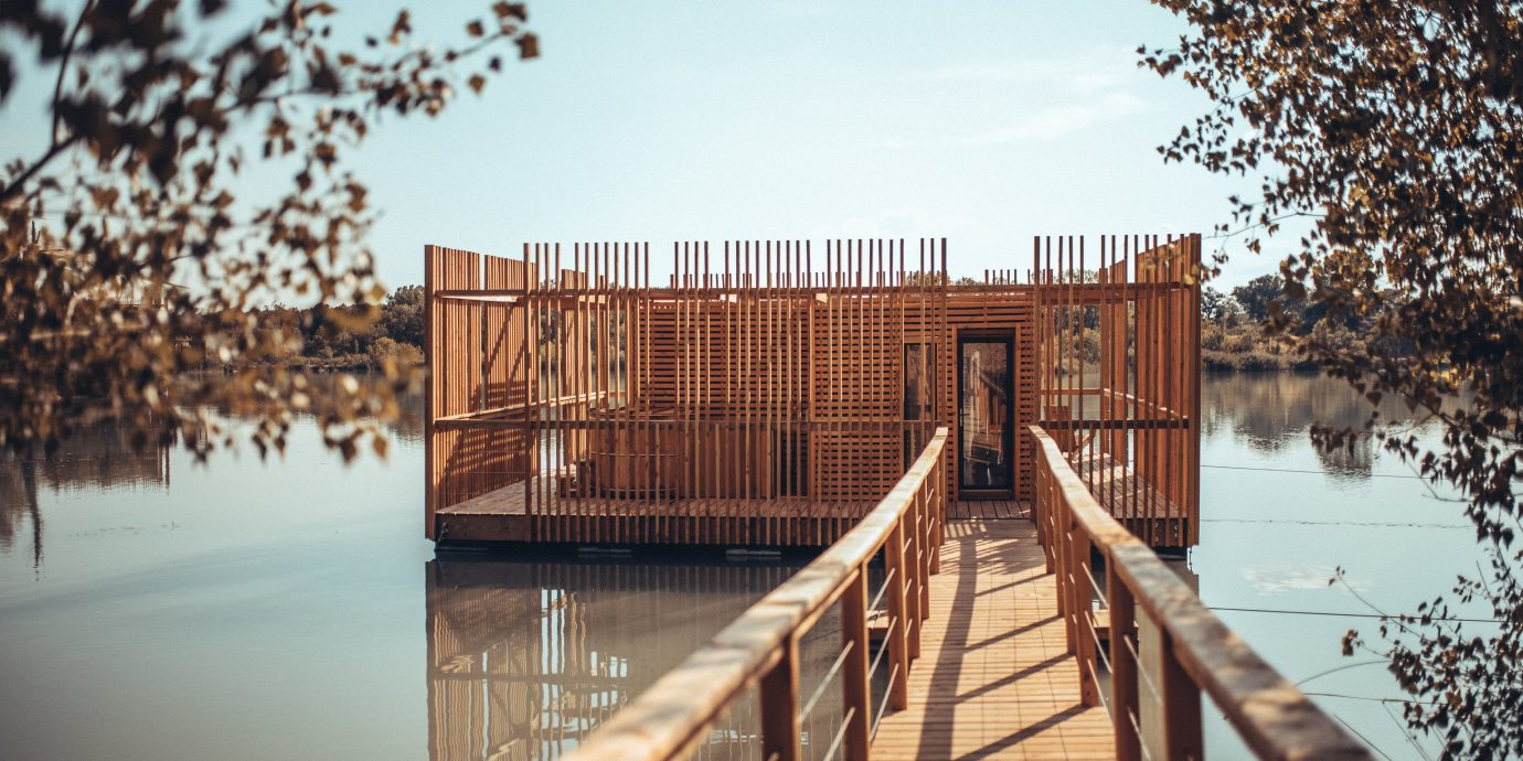 Hotels News Offbeat reflection water tree wood Winter bridge sky outdoor structure boardwalk