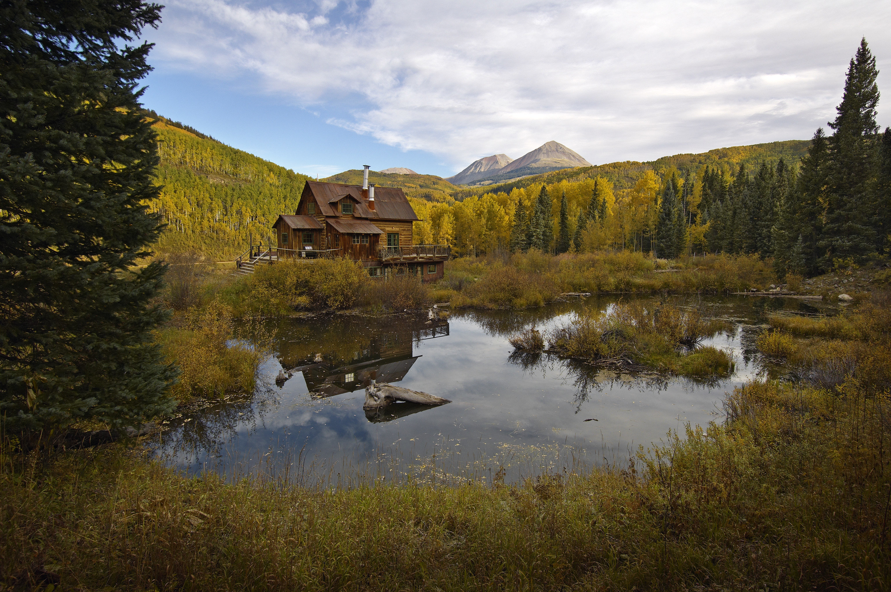 All-Inclusive Resorts Boutique Hotels Fall Travel Hotels Outdoors + Adventure Romance Trip Ideas tree outdoor sky grass reflection Nature wilderness tarn mountain mountainous landforms water leaf nature reserve Lake highland pond mount scenery loch national park fell landscape bank biome cloud wetland autumn hill tundra mountain range River valley larch meadow Forest surrounded lush hillside