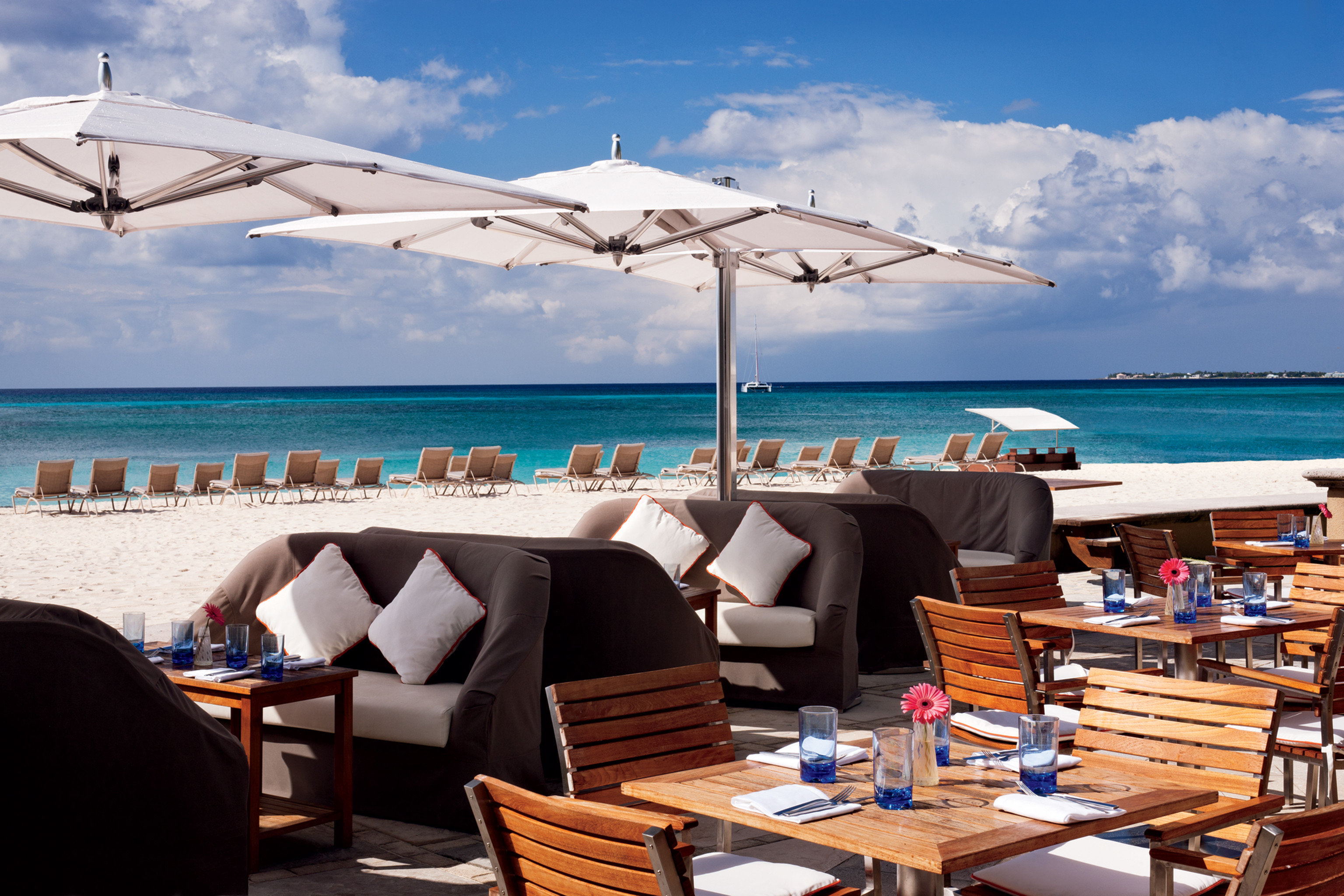 Bar Beachfront Dining Drink Eat Hip Hotels Luxury Modern sky water chair outdoor umbrella leisure passenger ship vehicle vacation Sea yacht ship caribbean Ocean Boat Resort marina luxury yacht dock watercraft set several shore furniture day