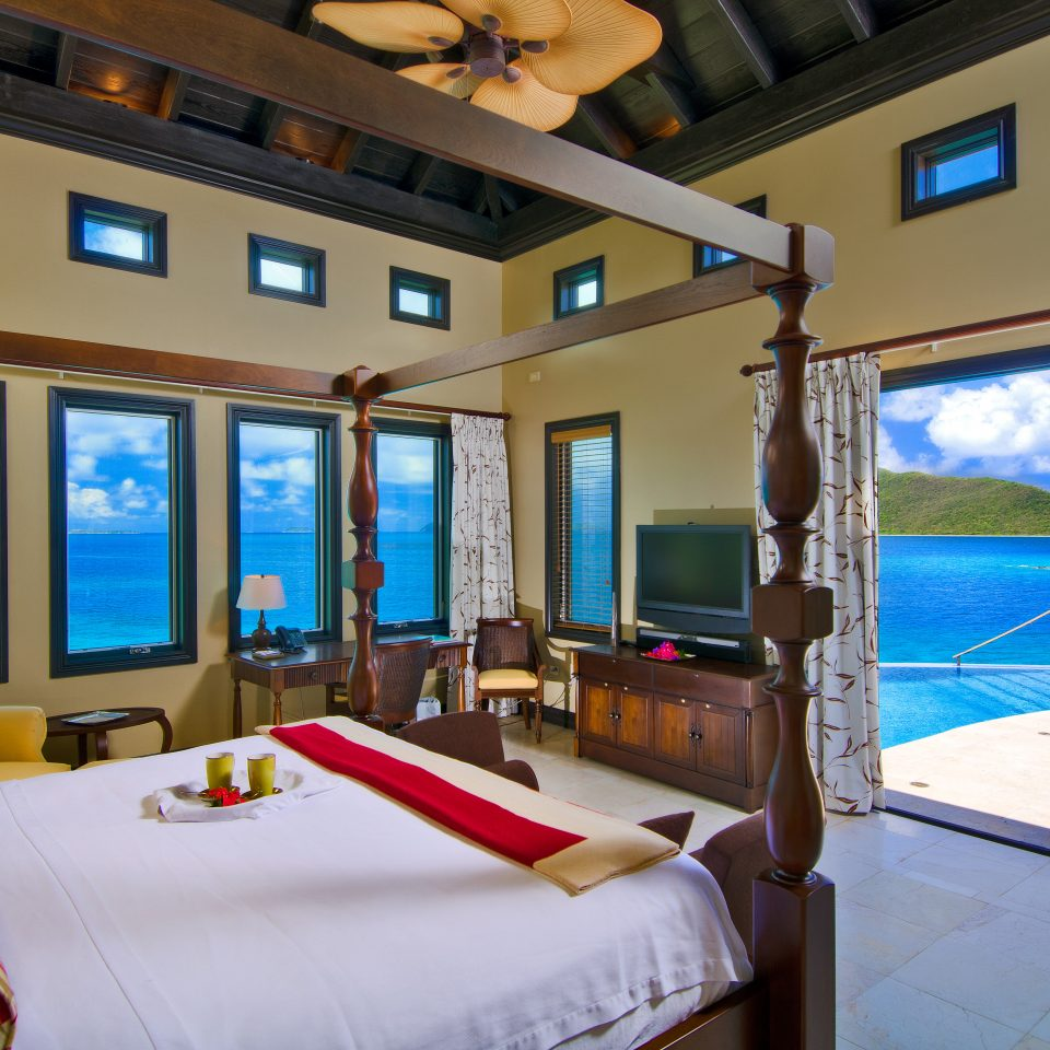 villa bedroom with numerous windows to see beautiful water view