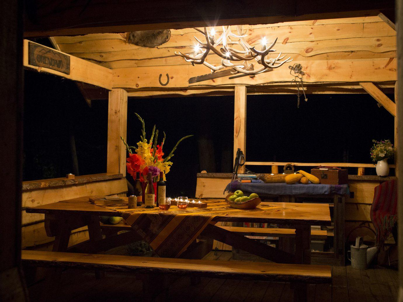 Glamping Outdoors + Adventure Weekend Getaways indoor table building room wood furniture home interior design window house restaurant night Fireplace dark