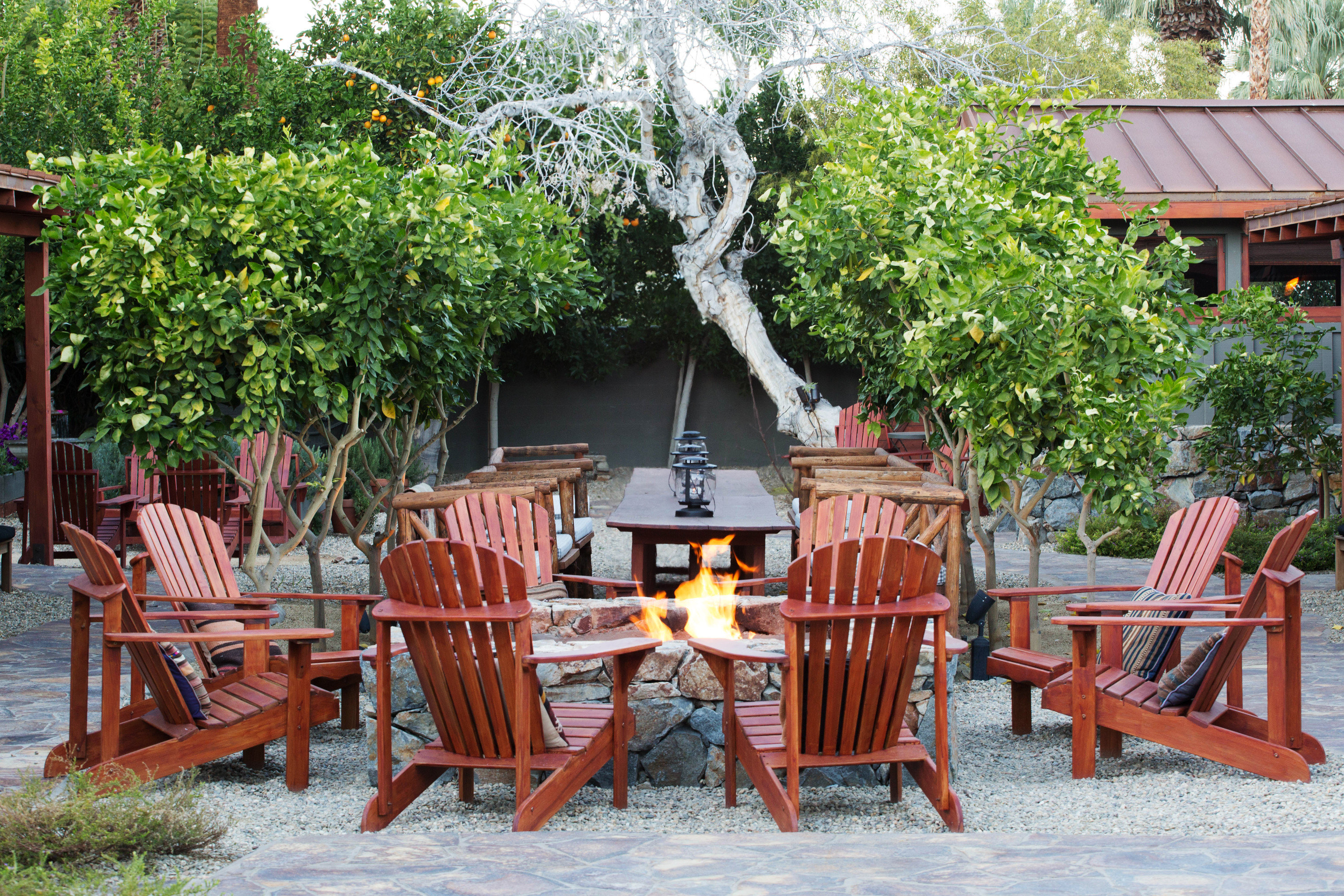 Influencers + Tastemakers Travel Shop Trip Ideas tree outdoor chair table backyard cottage Garden outdoor structure flower restaurant Resort Dining yard set porch area surrounded