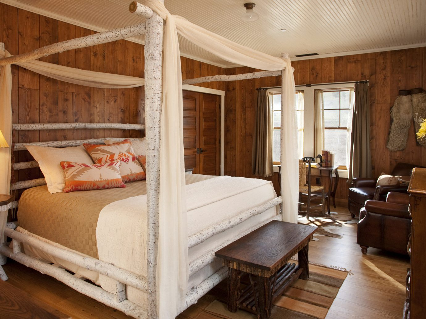 Glamping Luxury Travel Trip Ideas indoor floor room bed property Bedroom wooden cottage estate living room hardwood home Suite interior design four poster furniture wood log cabin farmhouse real estate