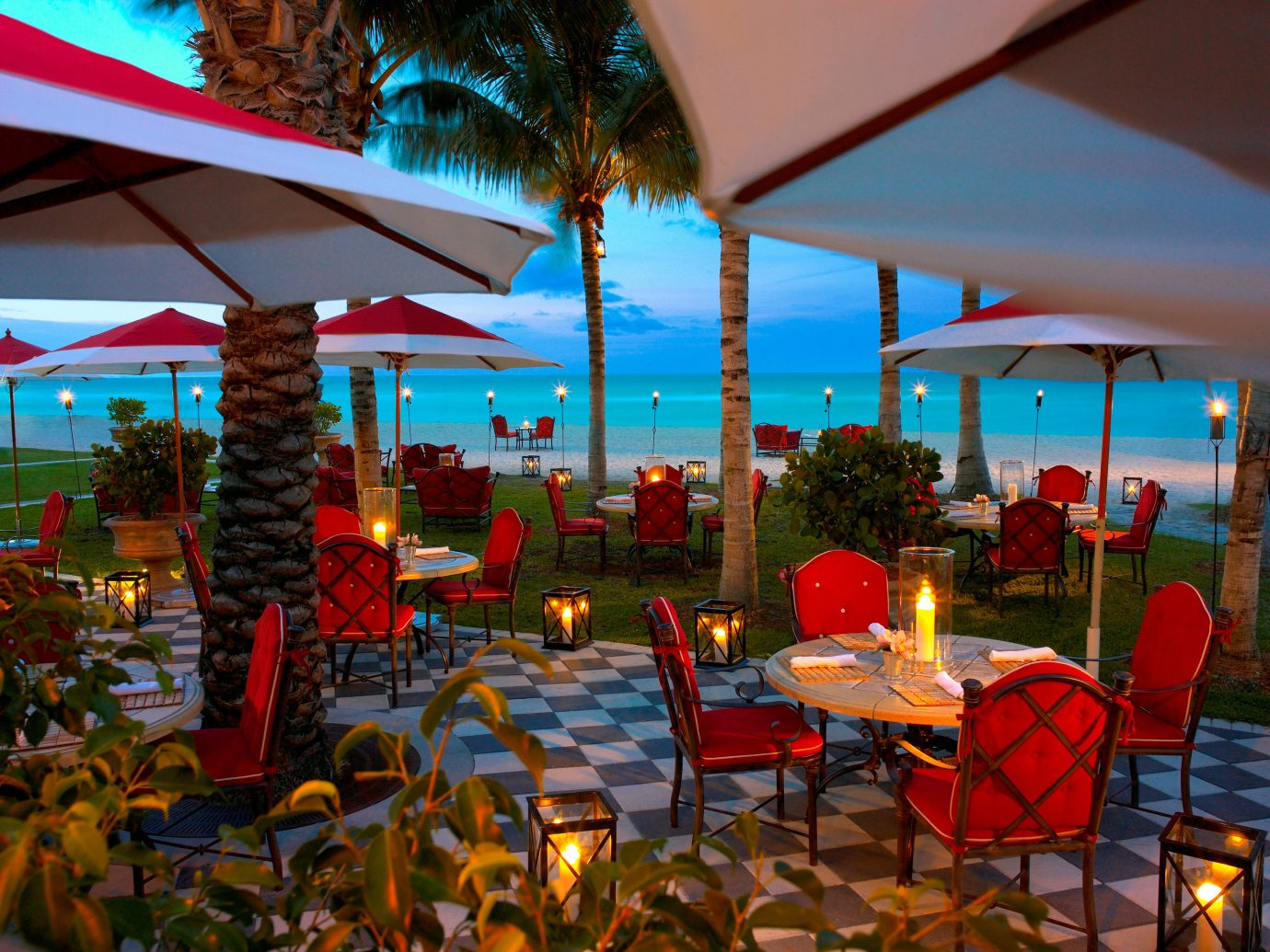 Beachfront Courtyard Dining Drink Eat Honeymoon Hotels Patio Romance Scenic views Terrace Waterfront umbrella chair outdoor Resort restaurant lawn vacation meal colorful set furniture several