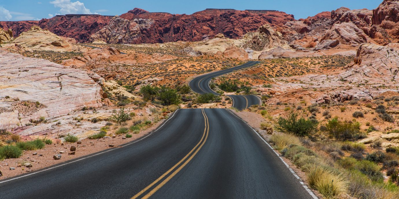 Road Trips Trip Ideas sky outdoor mountain grass road landform natural environment Desert highway infrastructure road trip landscape valley canyon wadi mountain pass badlands trail nonbuilding structure plateau traveling hillside