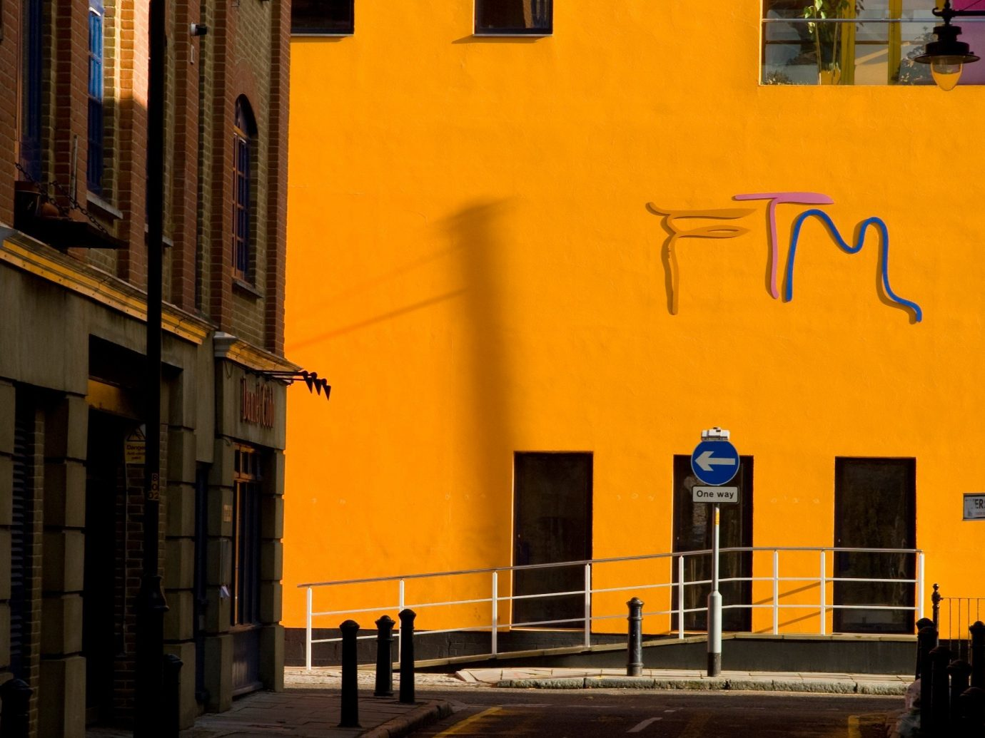 Jetsetter Guides building outdoor color road street urban area City yellow neighbourhood wall night Architecture facade Downtown evening infrastructure alley cityscape way sidewalk