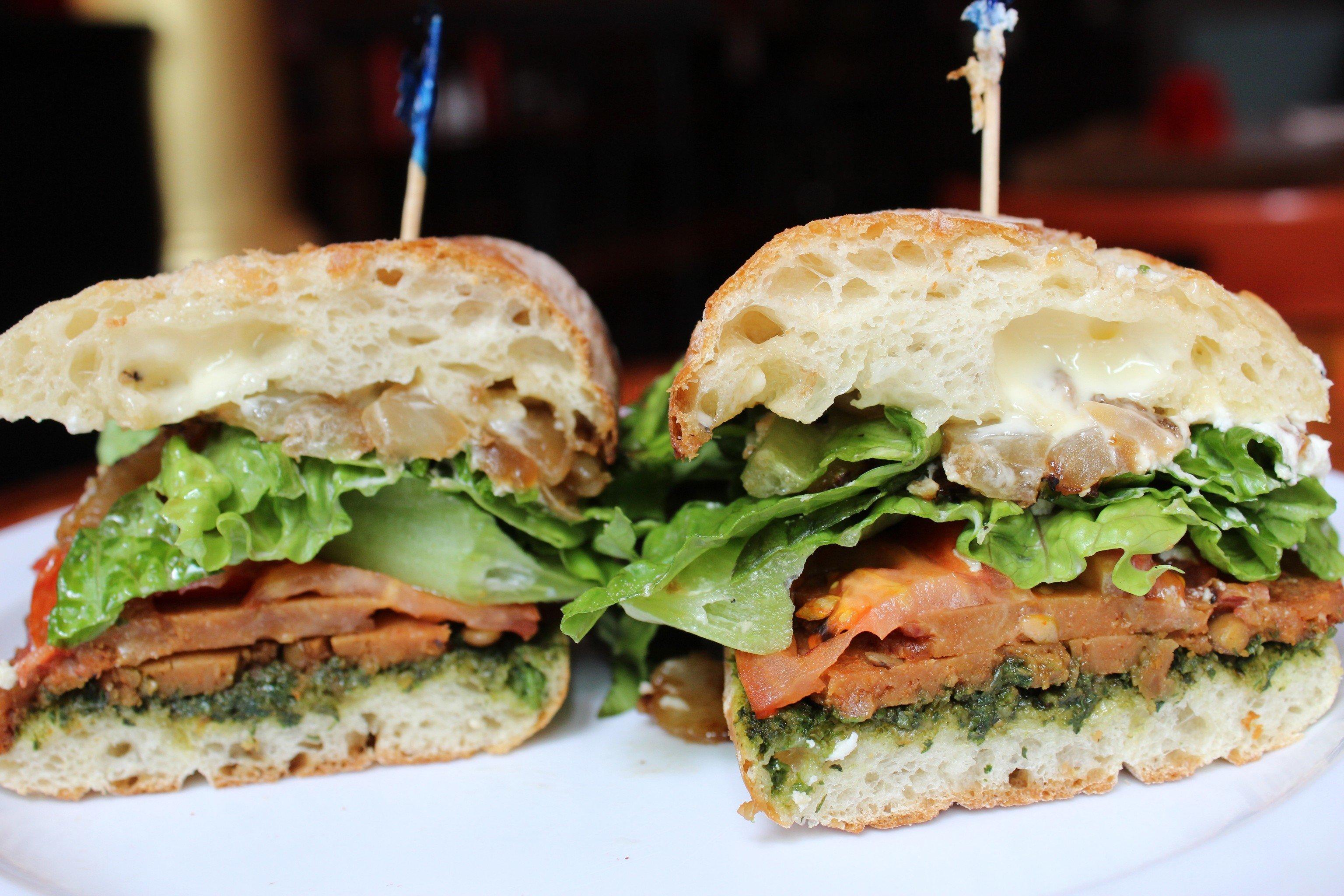 Food + Drink sandwich food plate dish snack food muffuletta half breakfast sandwich veggie burger cut blt white meal produce cuisine ciabatta hamburger meat close