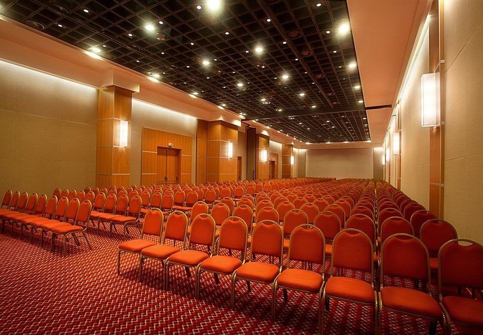 auditorium chair orange function hall conference hall convention center stage convention movie theater academic conference ballroom theatre audience meeting line