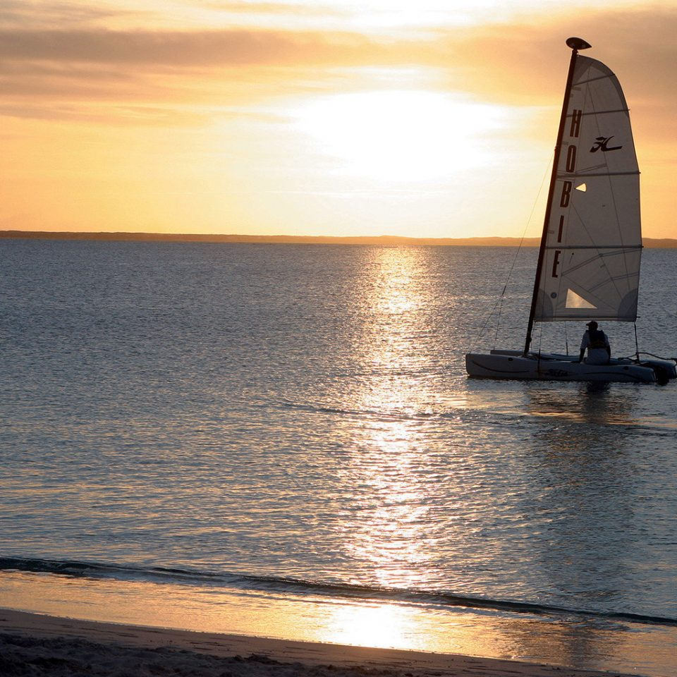 Adventure Boat Island Ocean Outdoor Activities Tropical water sky Sea Sunset horizon shore vehicle sunrise Coast sailboat sailing vessel watercraft Beach evening dusk wave dawn distance