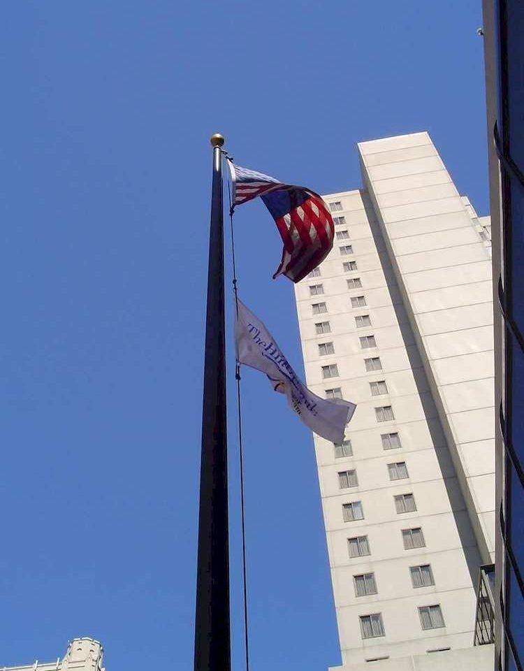 sky building blue skyscraper flag lighting advertising mast tower street light light fixture tall roof