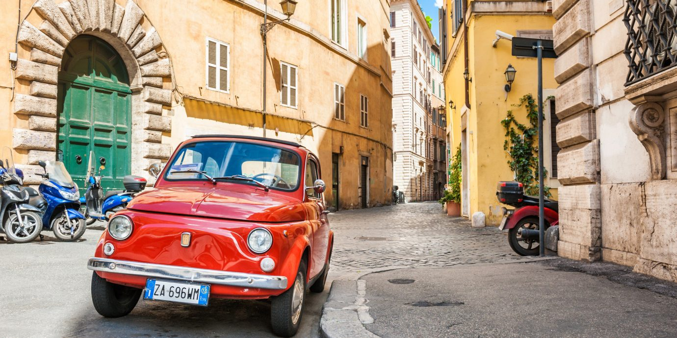 Travel Tips Trip Ideas building outdoor road car red street vehicle motor vehicle parked automotive design Classic city car way scooter stone compact car subcompact car City sidewalk family car vintage car fiat 500 old