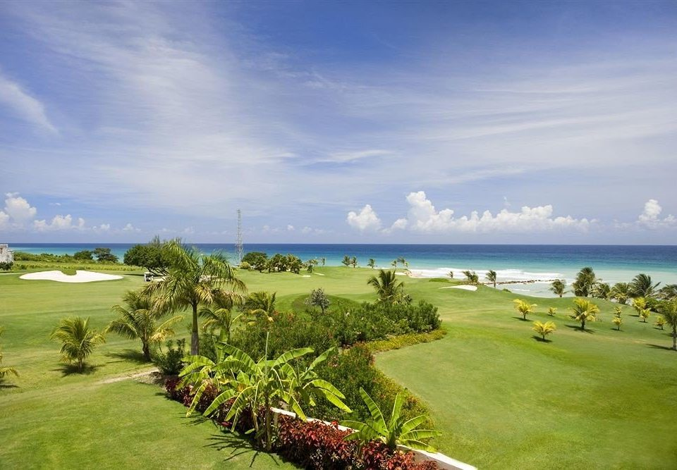 All-inclusive Beachfront Golf Tropical grass sky structure Nature sport venue Beach golf course shore Sea golf club Coast Resort caribbean sports cape grassy plant lush overlooking field