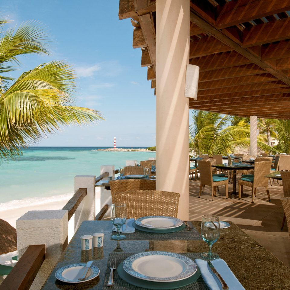 All-inclusive Beachfront Dining Drink Eat Luxury Ocean sky tree chair leisure property Resort swimming pool caribbean Villa home arecales restaurant overlooking set dining table