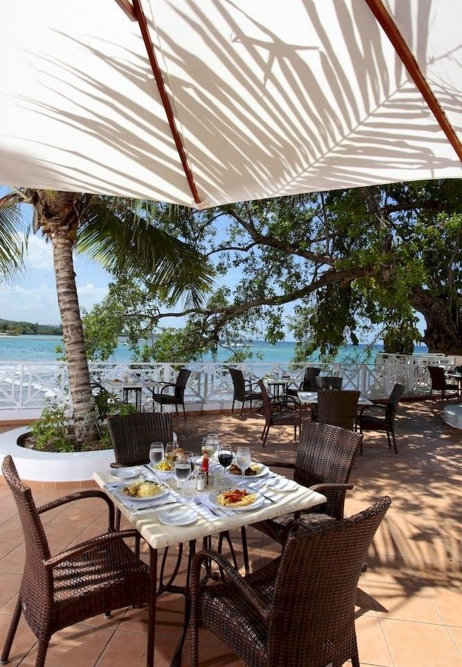 All-inclusive Beachfront Dining Drink Eat Grounds Patio Resort Scenic views Tropical tree chair umbrella restaurant outdoor structure Villa backyard