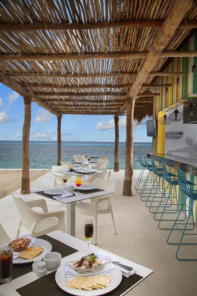 All-inclusive Beachfront Dining Drink Eat Modern Waterfront property Resort restaurant Villa home cottage dining table