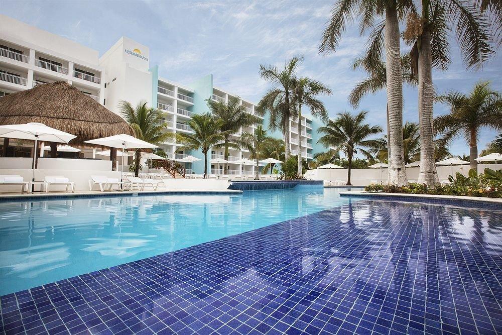 All-inclusive Beachfront Modern Pool Waterfront swimming pool property leisure Resort condominium reflecting pool blue resort town Villa backyard mansion day