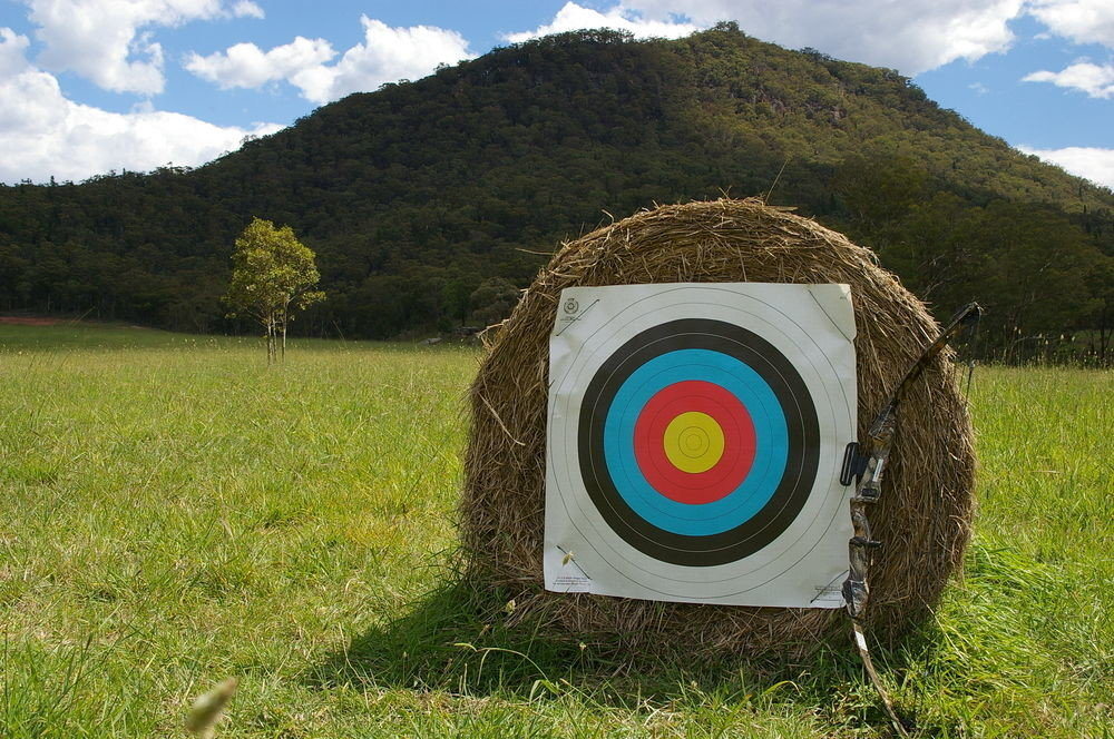 grass sky mountain man made object field sports outdoor recreation recreation rural area grassy archery individual sports hay outdoor object