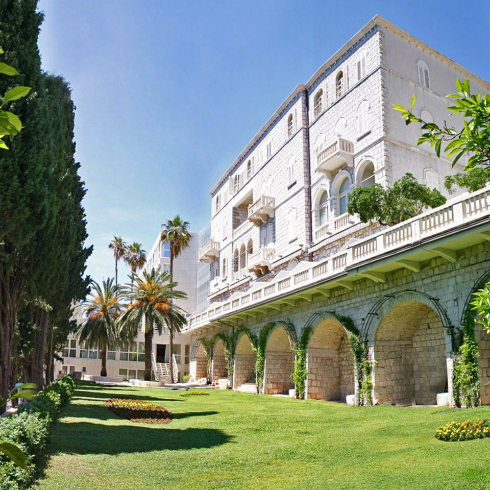 Beachfront Buildings Grounds Play Trip Ideas tree grass building stone landmark Architecture neighbourhood house green stately home mansion old Garden home Courtyard palace place of worship monastery arch colonnade