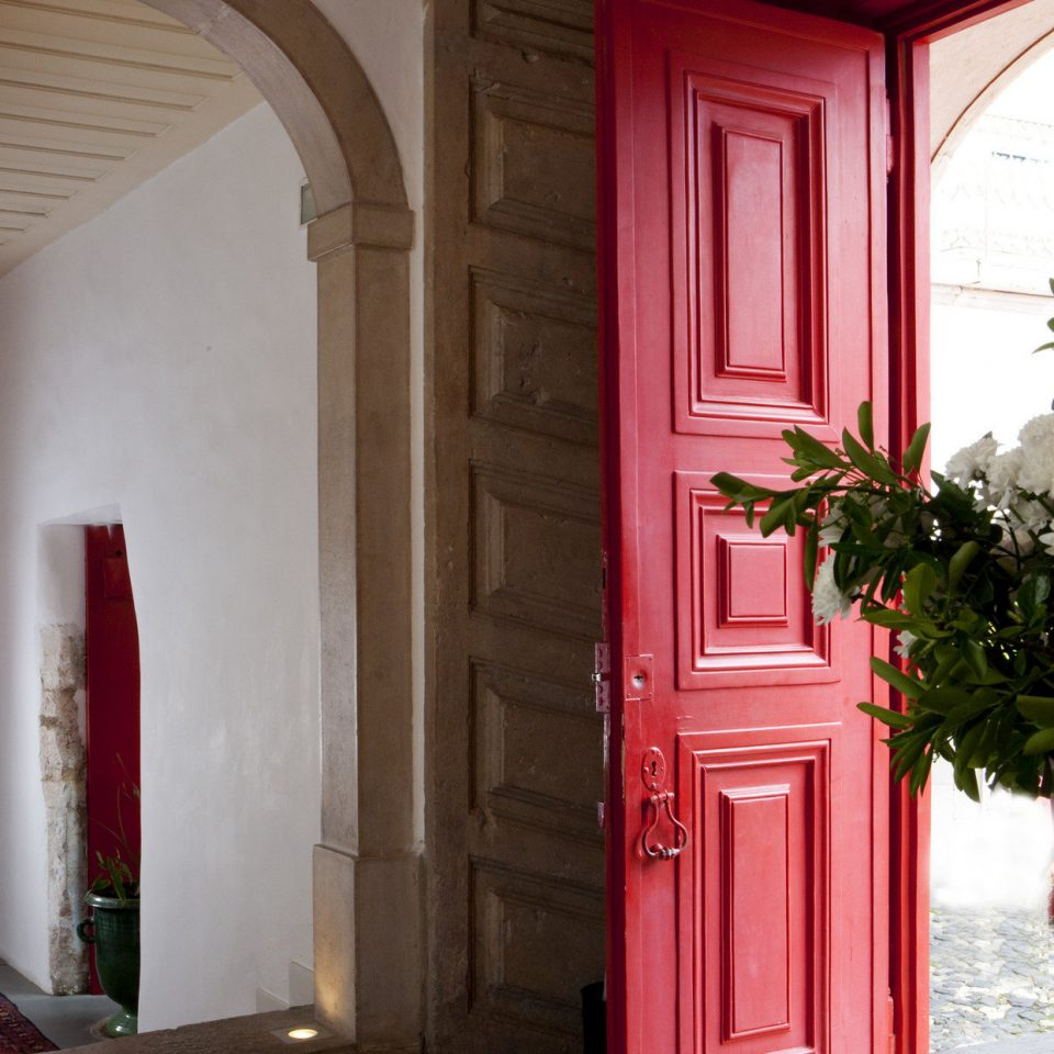 Boutique detail door Elegant foyer hall hallway Luxury regal sophisticated red color building house home Architecture arch living room plant stone