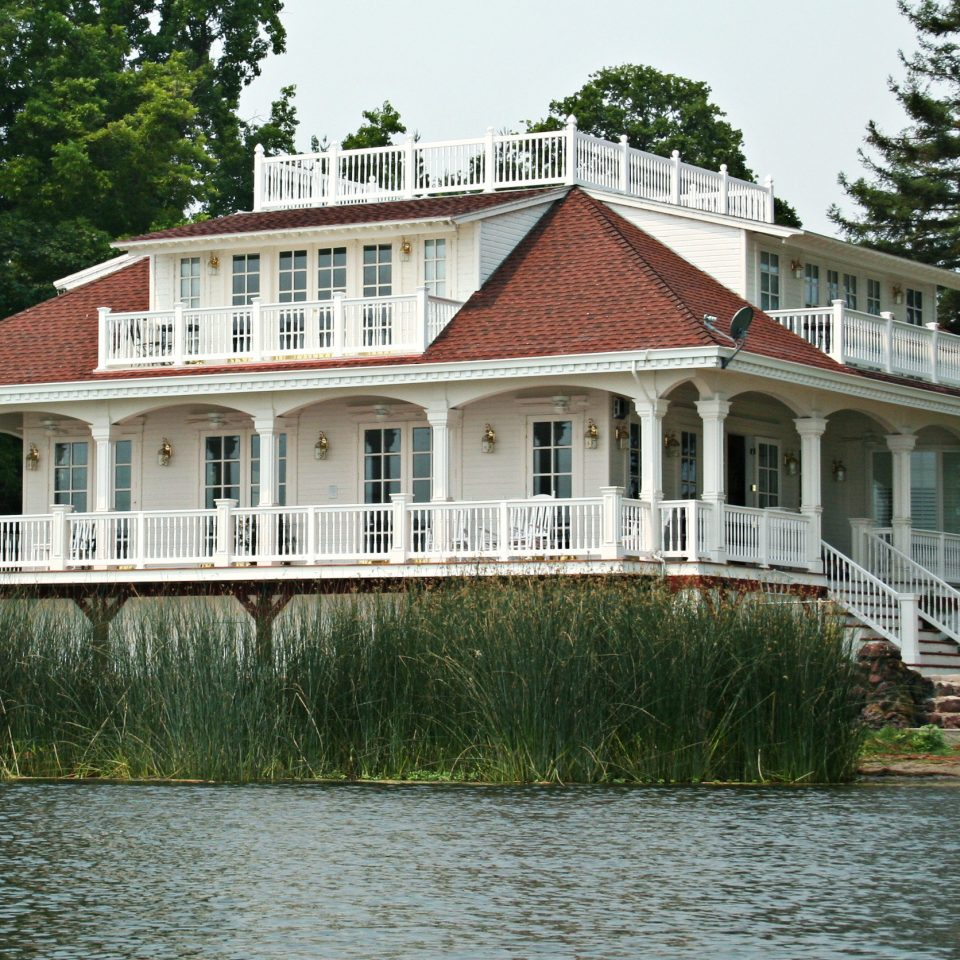 Architecture Buildings Exterior Grounds Waterfront tree house water building home boathouse Lake waterway manor house cottage residential mansion surrounded hillside