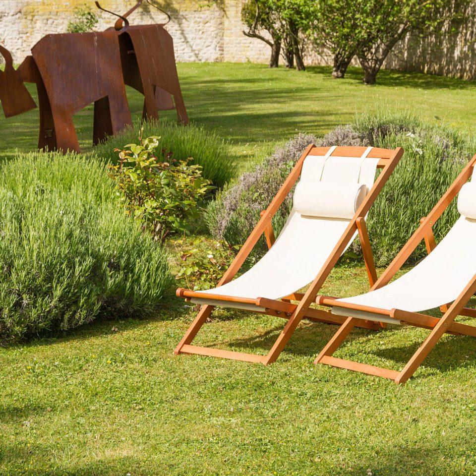 grass chair lawn seat leisure field grassy outdoor play equipment park backyard meadow swing set lush