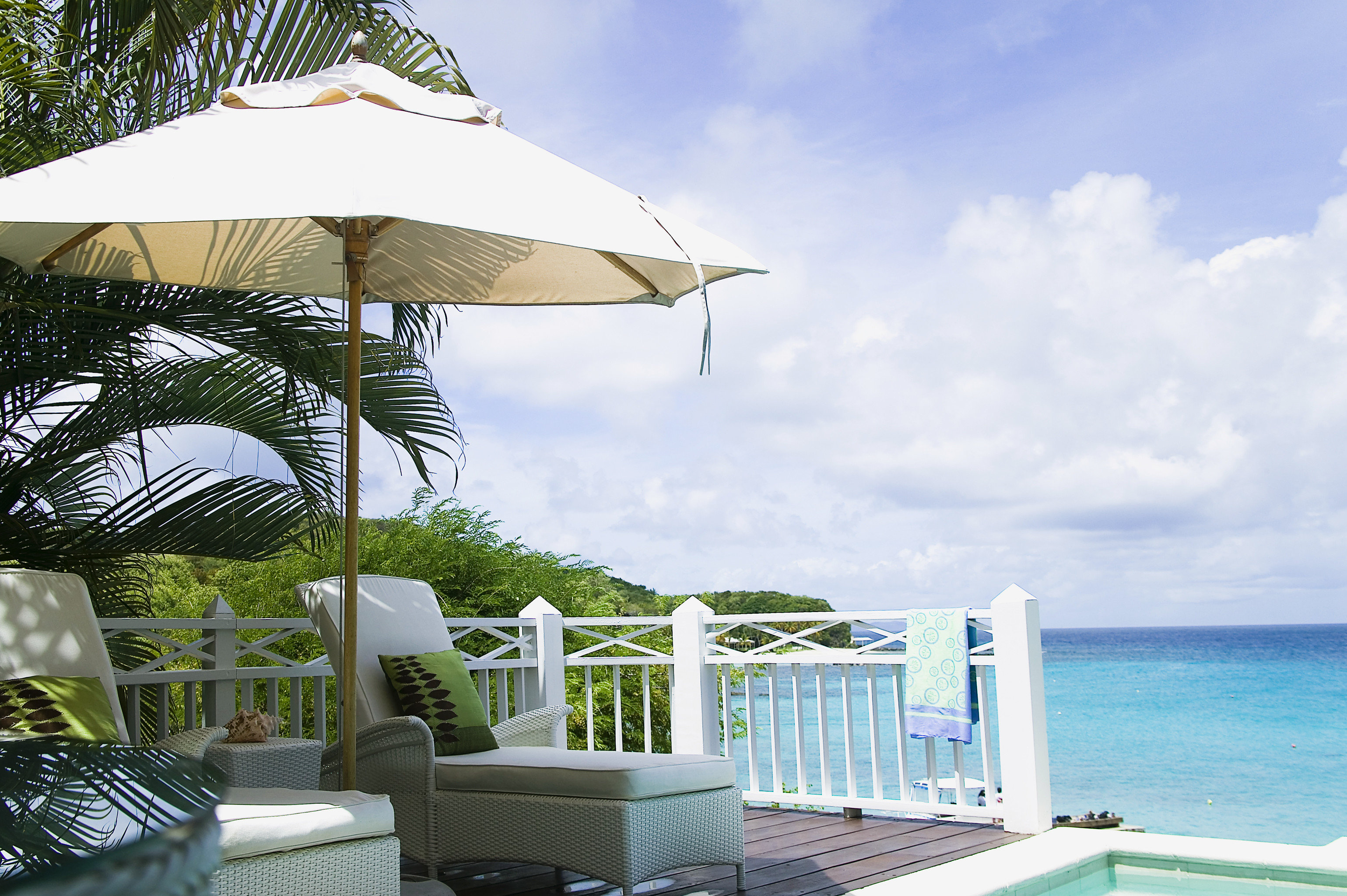Balcony Beachfront Deck Island Ocean Scenic views sky chair Beach caribbean Resort Villa umbrella swimming pool Sea cottage accessory