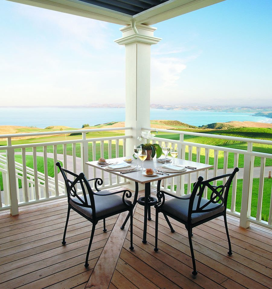 sky water chair property Beach overlooking Ocean Deck porch outdoor structure home Villa cottage metal Balcony sandy dining table