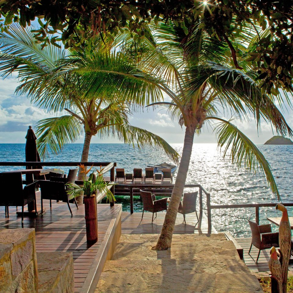 Balcony Dining Drink Eat Lounge Patio Resort Scenic views Waterfront tree water leisure Beach plant caribbean arecales Ocean Sea tropics palm family palm overlooking shade shore sandy Island