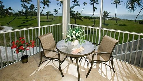 property chair Villa backyard home Balcony cottage outdoor structure porch Deck surrounded dining table