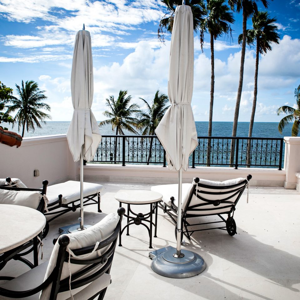 Balcony Lounge Patio Scenic views property house home Resort Villa condominium swimming pool backyard mansion living room palm