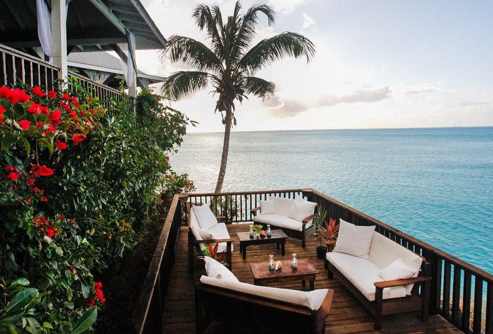 water Resort property Sea arecales palm tree Balcony tropics tree Ocean leisure condominium house Villa overlooking