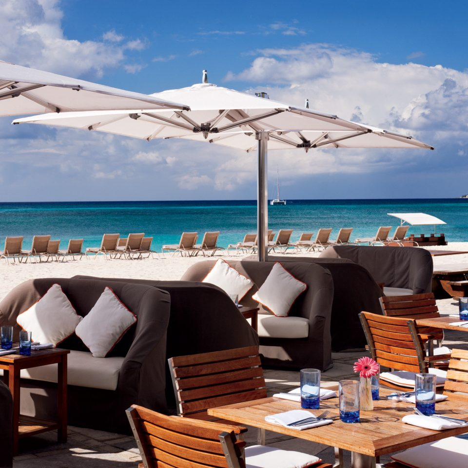 Bar Beachfront Dining Drink Eat Hip Hotels Luxury Modern sky water chair umbrella leisure passenger ship vehicle Sea yacht ship caribbean Ocean Boat Resort marina luxury yacht dock watercraft set shore day