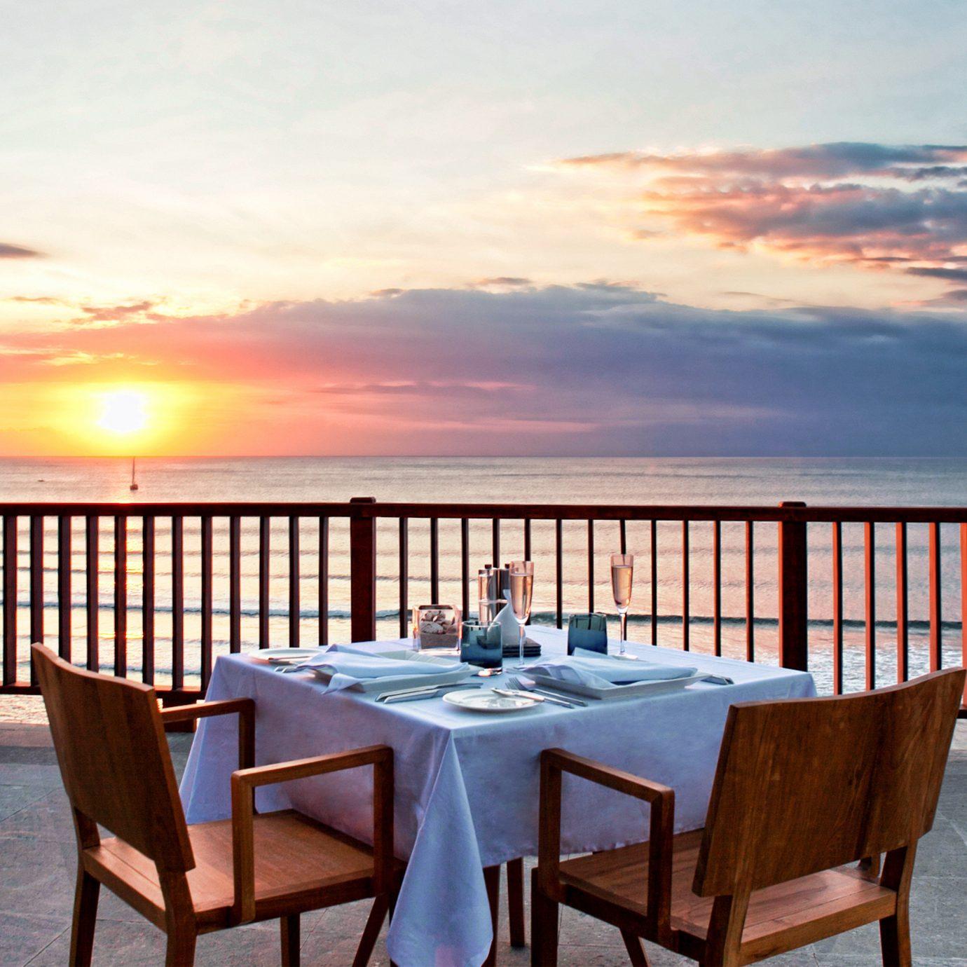 Bar Beachfront Dining Drink Eat Nightlife Scenic views sky chair water property Ocean overlooking Resort set dining table