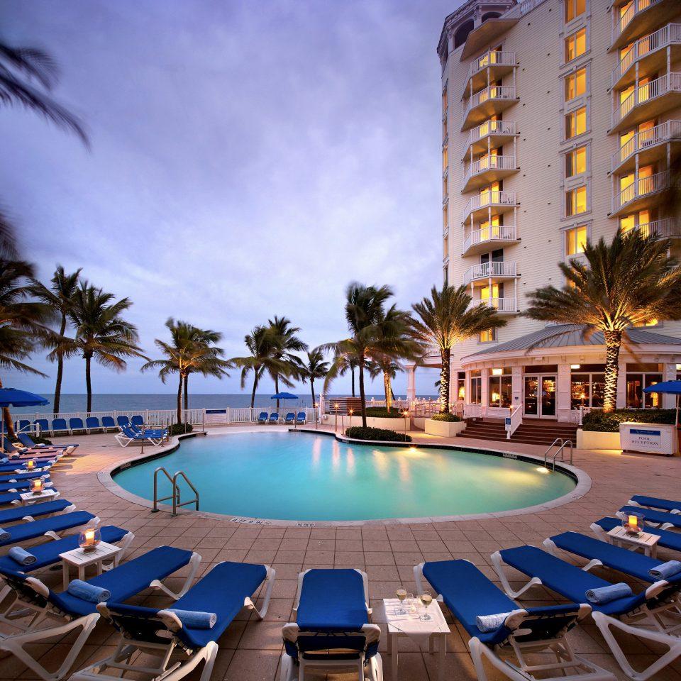 Bar Lounge Modern Pool Resort Scenic views Waterfront sky umbrella swimming pool leisure chair condominium palm lined marina blue Deck day