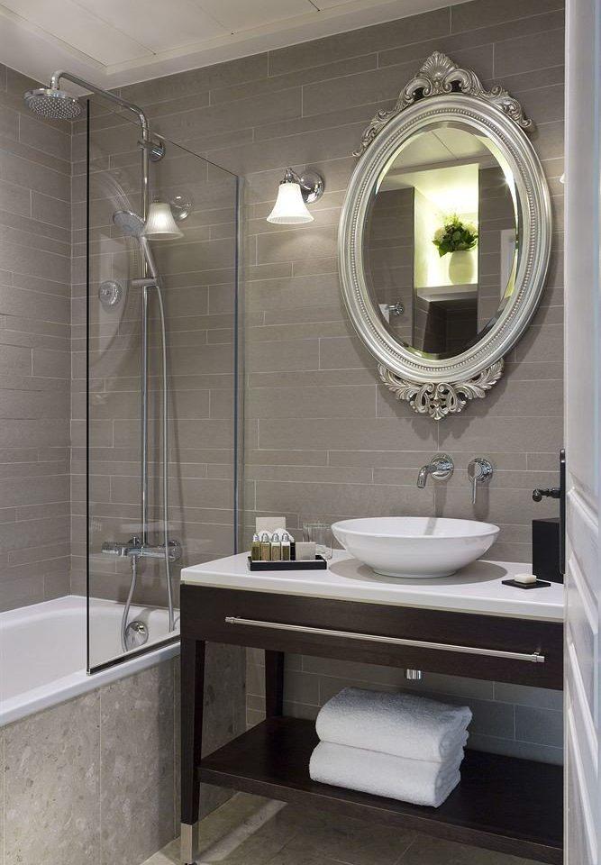 bathroom mirror sink plumbing fixture home flooring shower tile bathroom cabinet toilet Bath tub tiled bathtub