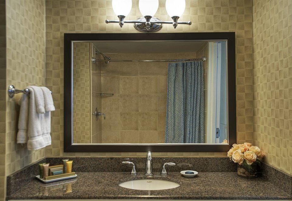 bathroom sink mirror towel plumbing fixture lighting flooring tile living room bathroom cabinet Bath tiled tan stone