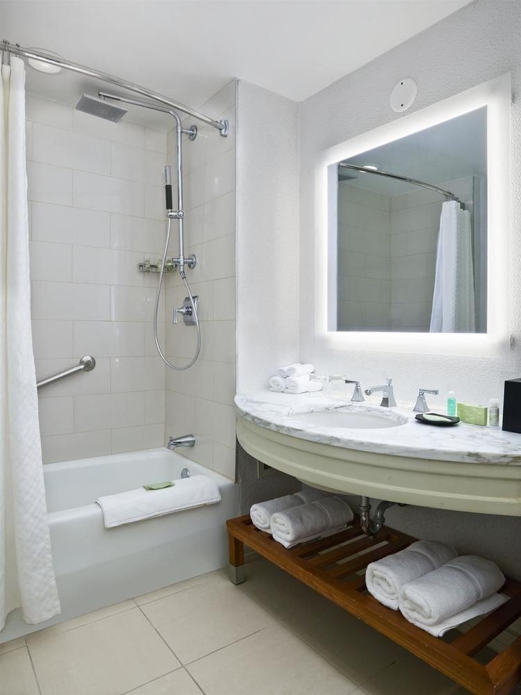 bathroom sink mirror property plumbing fixture white bathtub bidet toilet towel tub tile Bath tiled