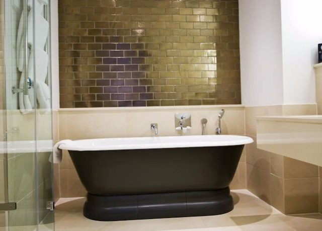 bathroom property bathtub tub plumbing fixture tile flooring sink bidet vessel Bath tiled