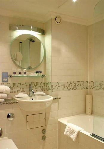 bathroom sink property mirror toilet plumbing fixture bidet flooring tub Bath bathtub