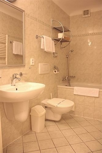 bathroom sink toilet property mirror bidet plumbing fixture flooring public toilet tile tiled tub bathtub Bath