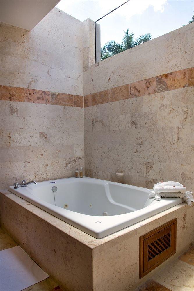 bathroom swimming pool vessel bathtub tub plumbing fixture jacuzzi old sink bidet Bath flooring dirty tiled tan tile stone